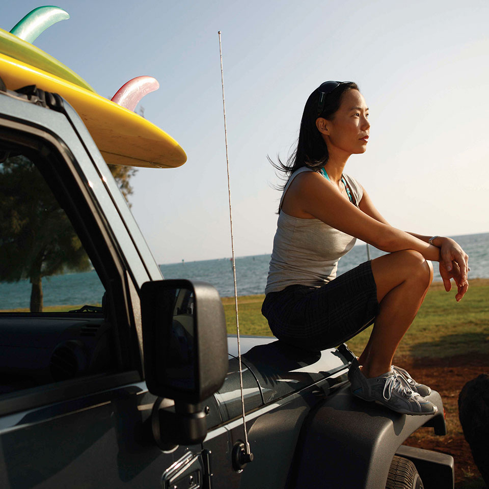 Female student sitting on a jeep before surfing, with ocean in background.