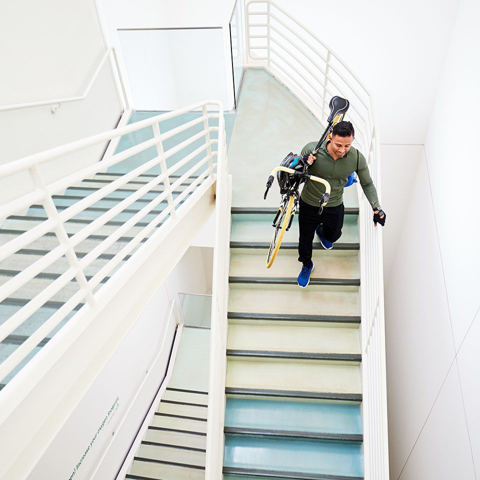 A young man carries a bicycle down a stairwell.
