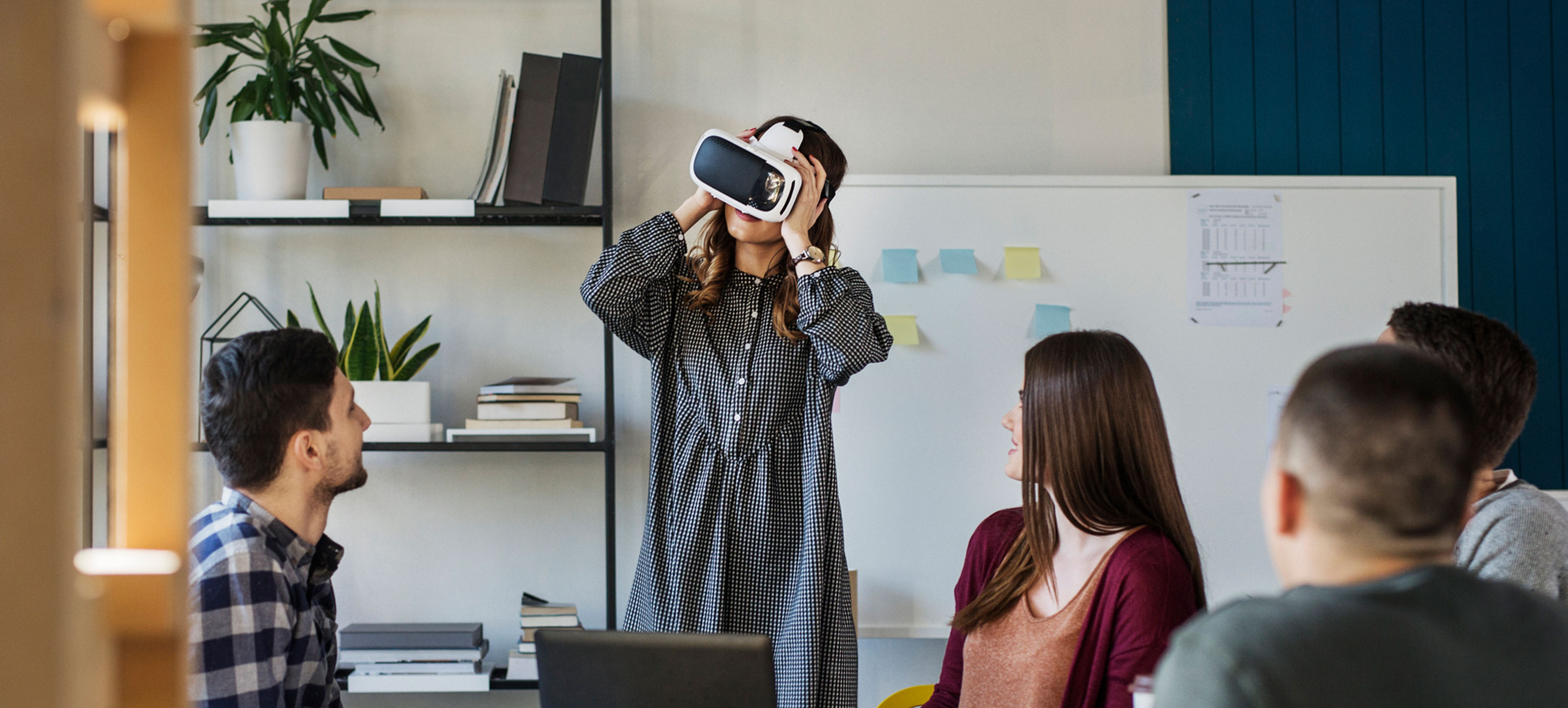 Medical students watch a classmate use a virtual reality headset.